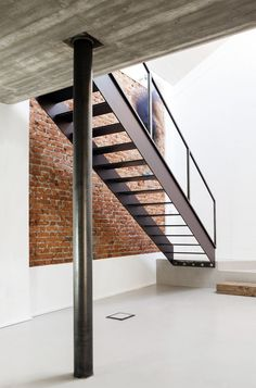 Black metal stairway with brick wall. U V House by O A S I architects. Photo by Stefania Matteo.