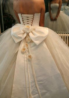Gorgeous ballgown wedding dress with corset back, bow, and trailing roses. Love everything except the flowers...