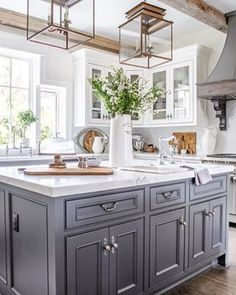Country Kitchen with Dark Center Island-double lantern pendants-honed marble countertops-white glass cabinets-french range hood Country Kitchen Designs, French Country Kitchens, Rustic Kitchen Design, Modern Farmhouse Kitchens, Home Decor Kitchen, Home Kitchens, Modern French Kitchen, Country Kitchens With Islands, Country Bathrooms