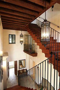 A view of the main staircase reveals an interior balcony overlooking the foyer and honed flagstone floors.