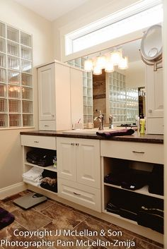 """""""her"""" side of the master bathroom with sink, tap and custom vanity with glass half wall for the shower"""