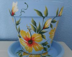 Hand painted Flower Pot & Matching Saucer *Tropical Design *Yellow and red Hibiscus Flowers on Light Blue Background Flower Pot Art, Flower Pot Design, Flower Pot Crafts, Painted Plant Pots, Painted Flower Pots, Flower Planters, Clay Pot Projects, Clay Pot Crafts, Decorated Flower Pots