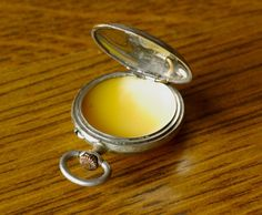 Solid Perfume in pocket watch  Materials  1 1/2 tsp. jojoba oil   essential oil (25 drops in original)  heaping 1/2 tsp. grated beeswax   small nonmetal pan for melting wax  shot glass or small cup  small compact or pillbox for finished perfume  Mix jojoba and essential oils in shot glass. Melt wax in bowl, add oils and heat 10 sec more. Pour into container and allow to set up.