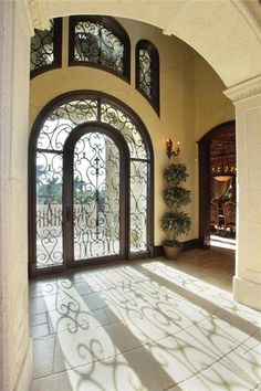 Mediterranean Entryway with Crystorama paris flea market 2 light wall sconce, Concrete tile , Wainscotting, Glass panel door