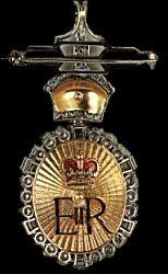 Back of Queen Elizabeth's royal family order - The back is 18 carat gold with the royal cypher and St Edward's Crown superimposed in gold and enamel. The chartreuse yellow riband bow is two inches wide.