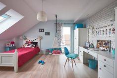 Przestronny pokój dziecięcy na poddaszu z kolorowymi dodatkami