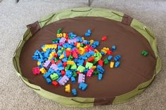 Play Mat filled with Toys that cinches up closed with drawstring leaving all the toys inside. This is a modified variation of one called the Lay-n-Go that are a little more pricey. I would probably enclose the cord instead of using grommets though.