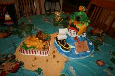 """Jake and the Neverland Pirates cake - 8"""" square cake, iced and decorated in buttercream, with a chocolate treasure chest and a fondant gator.  the 2 tier has fondant characters, map, cannons and shark fins.  Iced and decorated in buttercream"""