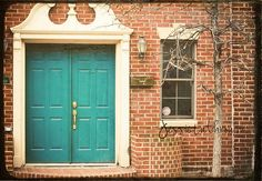 The orange in the brick is a complementary color of the turquoise door. (color wheel) That adds interest to this entry with no other elements. The off white softens the effect, as complements often 'vibrate' when placed side by side. (red-green, blue-orange, purple-yellow)