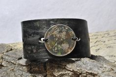 This leather cuff bracelet is made with recycled leather from a belt of mine that some how shrunk and can no longer be worn. The 1980 UK 10 New Pence coin is attached using waxed cotton cord.  On the back of the bracelet are silver color eyelets where chain and a toggle clasp connect. The coin and leather are hand painted to look old and worn.