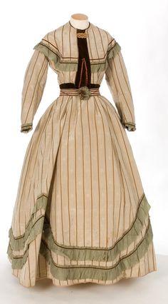 1850-1860 beige dress with moss green trimming. Via IMATEX.