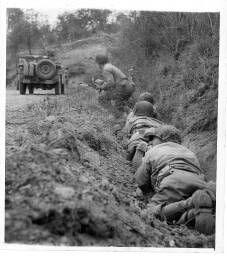 During the fighting at Saint Lô, American soldiers leaving their jeep in the road on meeting german mortar and machine gun fire ... = [Au cours de la bataille de Saint-Lô, les membres d'équipage d'une jeep, tombés sous le feu d'une mitrailleuse et d'un mortier allemands, se sont réfugiés dans un fossé].