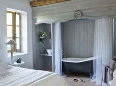 I like the idea of being able to shut the curtains to hold in the heat around the bath...Restored Farmhouse in France | Inspiring Interiors