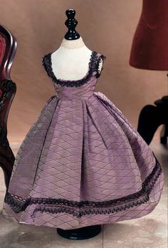 Crisp mauve silk taffeta dress trimmed with delicate black Alencon lace, designed to be worn over a chemisette. Low rounded neckline, fitted bodice, and a widely-flared skirt with wide double-box pleats. Circa 1860.