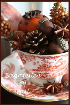orange detailed cup and saucer, filled with potpourri of persimmon, acorns, anise, pinecones, peppercorns