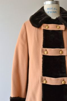 Vintage 1960s camel wool coat, very soft with soft black faux fur trim, gold double breasted buttons, wide sleeve cuffs and full lining.