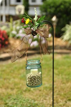 Old glass canning jars with chick peas, candle and copper hanger for use in an outdoor wedding.