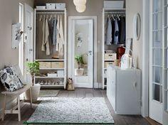 Předsíň s úložným prostorem od podlahy po strop, který se skládá z bílých polic a šatních tyčí na ukládání oděvů, tašek a obuvi. Na obrázku jsou také dvě bílé komody a lavice z bíle mořené masivní břízy.