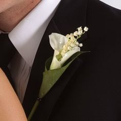 Tuck a sprig of filler flower and glue inside the calla lily with floral adhesive.