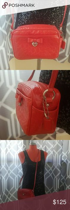 """Gorgeous little Authentic Coach crossbody In excellent condition inside and out. Red patent leather with cignature C's. One pocket on the front perfect for a cellphone and little pockets on each side. Super cute bow with heart that says Coach. 7"""" W x 5"""" H x 3"""" D. The strap hang 22"""" long in this pic but also is adjustable shown in last pic. Coach Bags Crossbody Bags"""