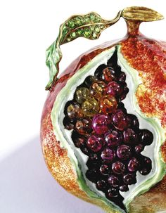 A Gold, Gem-Set and Enamel Table Ornament, Verdura the fanciful pomegranate highlighted in vibrant multi-colored enamel, with numerous ruby, pink tourmaline and citrine 'seeds,' the stem and leaves set with round demantoid garnets and colored diamonds weighing approximately .35 carat, unsigned. With signed and fitted box.
