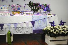 Bandeirinhas roxas e lilases enfeitaram a mesa do aniversário da Marina de 1 ano. A festa contou com muitas flores e cata-ventos e um painel com corações de papel.