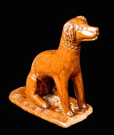 Price Realized: $ 3,450.00  Very Rare Glazed Redware Figure of a Dog, attributed to Solomon Bell, Strasburg, VA, third quarter 19th century, hand-modeled seated dog on base, with impressed eyes and incised details to face, ears, and paws. An unusual impressed collar and chain extends around the neck and down the back of the figure, reminiscent of the impressed chains and collars found of Bell family molded sp