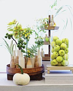 Inkwells are used as vases for autumn fern, feverfew, and chamomile. Green apples are a simple, inexpensive decor idea.