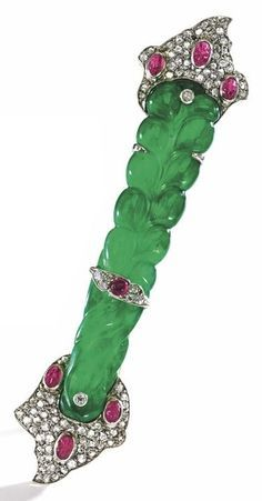 Platinum, Jadeite, Diamond and Ruby Brooch, Cartier, Circa 1925. Set with a Qing Dynasty carved jadeite hairpin section of emerald green colour, flanked on both ends by an asymmetrical motif, set throughout with rose-cut diamonds, carved cabochon rubies, and a cabochon ruby, signed Cartier,