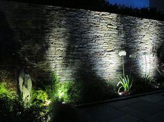 éclairage extérieur en projecteurs LED pour souligner le mur en pierre