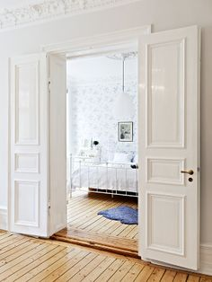 white french paneled doors to bedroom in apartment in gothenburg, sweden (photo via brokerage firm stadshem.se) (HT llamasvalley.blogspot.com)
