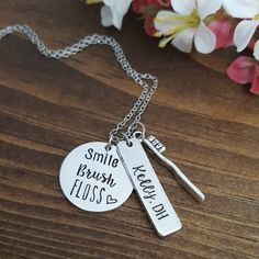 Personalized Dental Hygienist Necklace or Dental Assistant Necklace includes the following: • 7/8 Round Disc (Smile Brush Floss) • 1.125 Rectangle Tag • Antique Silver Toothbrush Charm • Stainless Steel Chain • Organza Gift Bag • Gift Box Option available here: https://www.etsy.com/listing/205195214/gift-wrap-my-item-with-optional-blank?ref=shop_home_active_3 TO PLACE ORDER: Copy & Paste into Notes section during checkout: • Text for 1.125 Rectangle Ta...