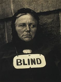 PAUL STRAND (American, 1890–1976): Blind, 1916  - Platinum print  This seminal image of a street beggar was published in 1917 as a gravure in Stieglitz's magazine Camera Work and immediately became an icon of the new American photography.