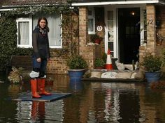 Resident Holly Phillips stands on a box outside her house after the river Thames flooded the village of Wraysbury, southern England February 10, 2014.