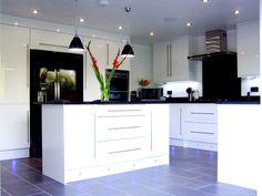 Bespoke gloss white kitchen and black quartz worktops.