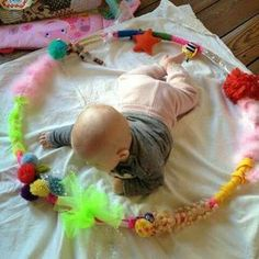 Baby sensory idea: textured hula hoop The children will engage in a multi-sensory experience (sight, sound, & texture). The children will strengthen core and arm muscles by reaching with arms. Baby Sensory Play, Baby Play, Diy Sensory Toys For Babies, Baby Sensory Ideas 3 Months, Baby Sensory Bags, Sensory Wall, Sensory Boards, Infant Activities, Activities For Kids