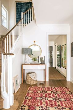 Modern traditional entryway - white walls, wood floors, tribal rug, modern walnut and white modern console
