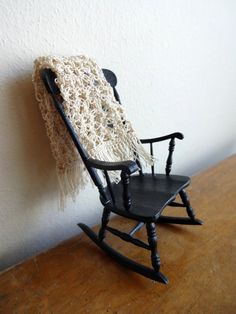rocking chair and crocheted beige blanket