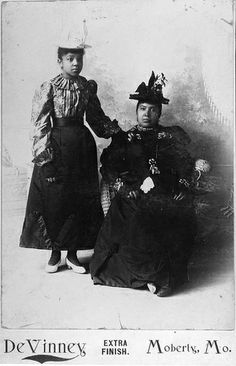 African American Woman and Girl: African American woman seated with girl standing to her side, both are wearing hats. c1890s Want to know more about Black History ? Visit Discover Black Heritage.