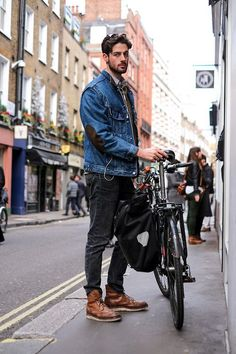 Shop this look on Lookastic: http://lookastic.com/men/looks/long-sleeve-shirt-v-neck-sweater-denim-jacket-jeans-brogue-boots/9348 — Grey Long Sleeve Shirt — Olive V-neck Sweater — Blue Denim Jacket — Charcoal Jeans — Brown Leather Brogue Boots