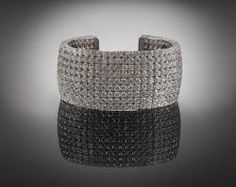 $146,150.00   An amazing 440 round brilliant-cut diamonds, weighing 52.61 total carats, adorn this exceptional diamond and 18K white gold cuff bracelet by Norman Silverman. The exquisitely matched diamonds are featured in two different sizes, with 414 larger stones gracing the main body of the cuff, and 26 smaller pavé set stones decorating the outer.