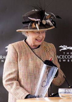 Queen Elizabeth II collects her trophy after her horse 'Sign Manual' won The Dreweatts Handicap Stakes at Newbury Racecourse on 19 April 2013 in Newbury