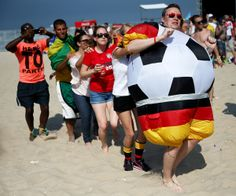 German and other soccer fans create a conga line while waiting for the start of the German vs. Portugal match as they watch on a giant screen at the FIFA World Cup Fan Fest on Copacabana beach on June 16, 2014 in Rio de Janeiro, Brazil. The teams are playing on the fifth day of the World Cup tournament. (Photo by Joe Raedle/Getty Images)