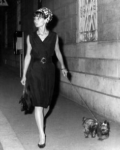 The Fashion of Audrey The actress Audrey Hepburn with her dog (Assam of Assam) on a shopping spree at Via dei Condotti in Rome (Italy), in March 1964. -Audrey was wearing dress and belt of Yves Saint Laurent (of his collection for the Spring/Summer of 1962), turban hat of Givenchy, handbag of Cartier Ltd. London and René Mancini shoes.