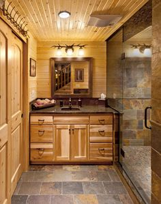 The slate floor you could see in the family room is carried into the bathroom and the shower stall.   The planked walls and pine cabinetry still keep that rustic feel.  The shower is nice and big.
