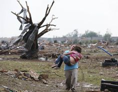 """Hold on"" photo by Sue Ogrocki/AP. A mother carries her child through a field near the collapsed Plaza Towers Elementary School in Moore, Oklahoma."