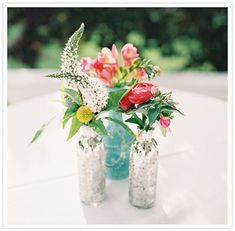 colorful wild flowers and silver bottle vases