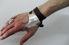 Metal and leather urban-tribal bracelet by Yohan Serfaty, as seen in Catching Fire, during the end-of-tour party at the Capital. Reminds me of an archery hand guard.