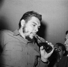 Ernesto Che Guevara, na época Ministro da Indústria cubano, bebendo Coca-Cola, em 1961, em Punta del Este, no Uruguai.    Che Guevara, um dos líderes da Revolução Cubana, foi flagrado bebendo o refrigerante considerado como o símbolo do capitalismo e do imperialismo estadunidense, durante um dos intervalos da Conferência Econômica e Social Inter-América, em agosto daquele ano.    Autor da foto: Desconhecido.
