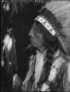 A portrait of Young Red Cloud, a Sioux man, wearing a feather headdress.  Oglala Sioux Tribe of the Pine Ridge Reservation, South Dakota.  Collection Richard Throssel.  Date Original: 1902-1933.  University of Wyoming. American Heritage Center.